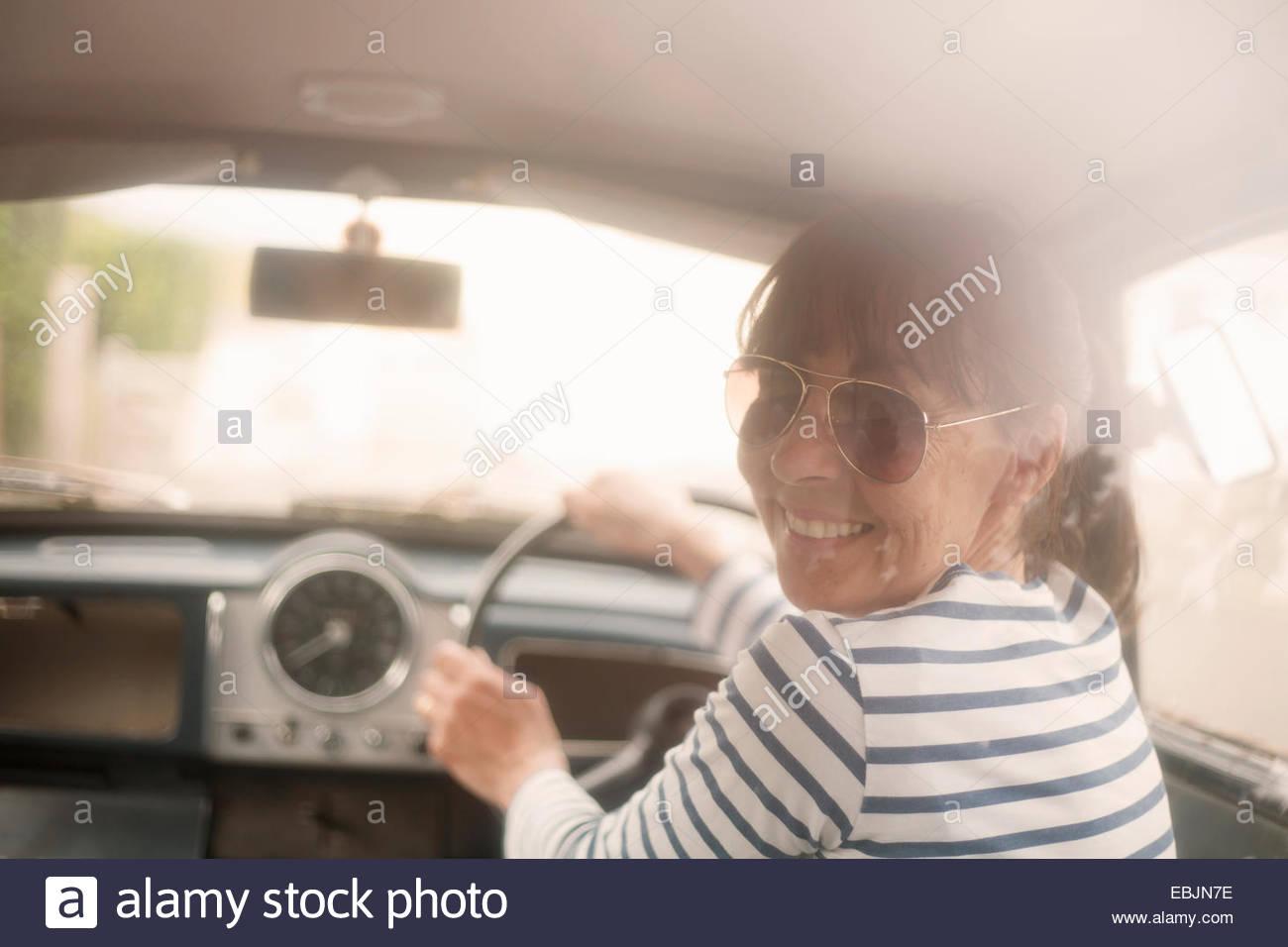 Mujer conduciendo un coche, sonriendo Imagen De Stock