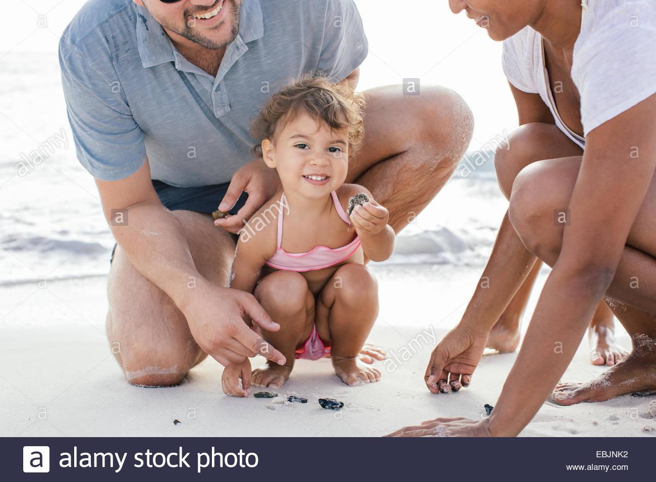 Pareja con dos chicas buscando conchas en la playa, en la Toscana, Italia Imagen De Stock