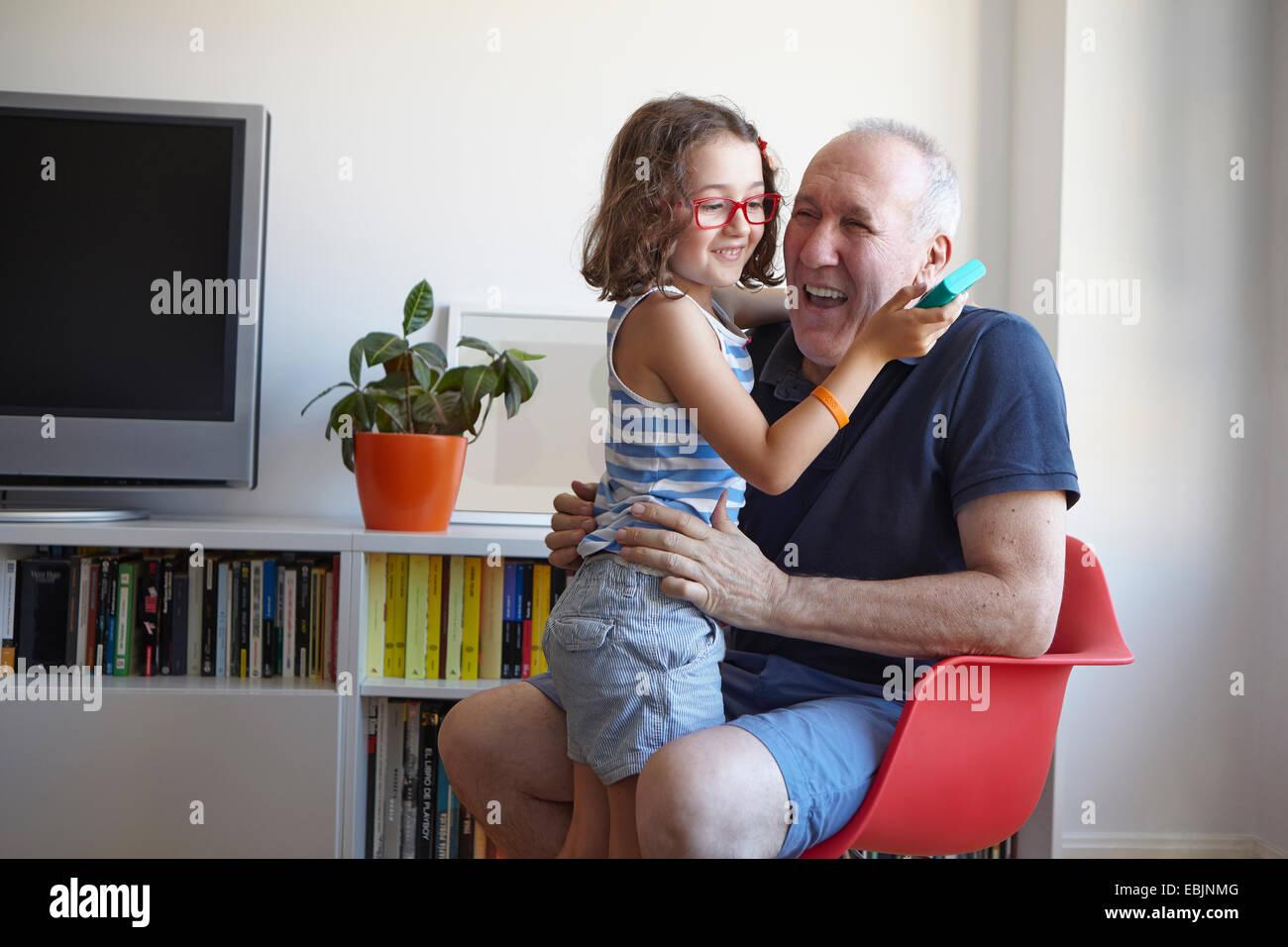 Chica y abuelo riendo mientras juega al juego de computadora de mano Imagen De Stock