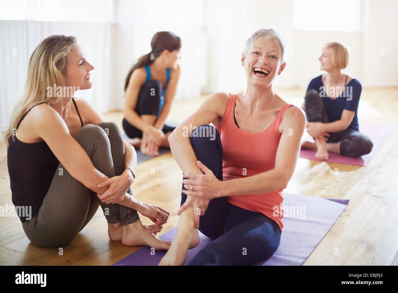 Cuatro mujeres sentadas en el suelo en clase de pilates Imagen De Stock