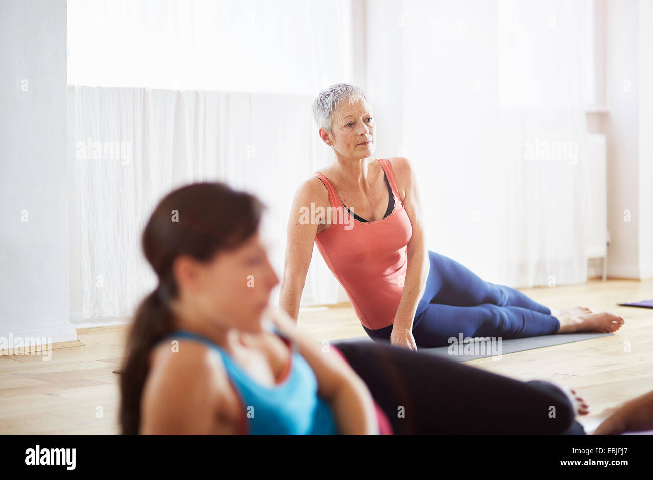 Dos mujeres acostado en el lado en clase de pilates Imagen De Stock