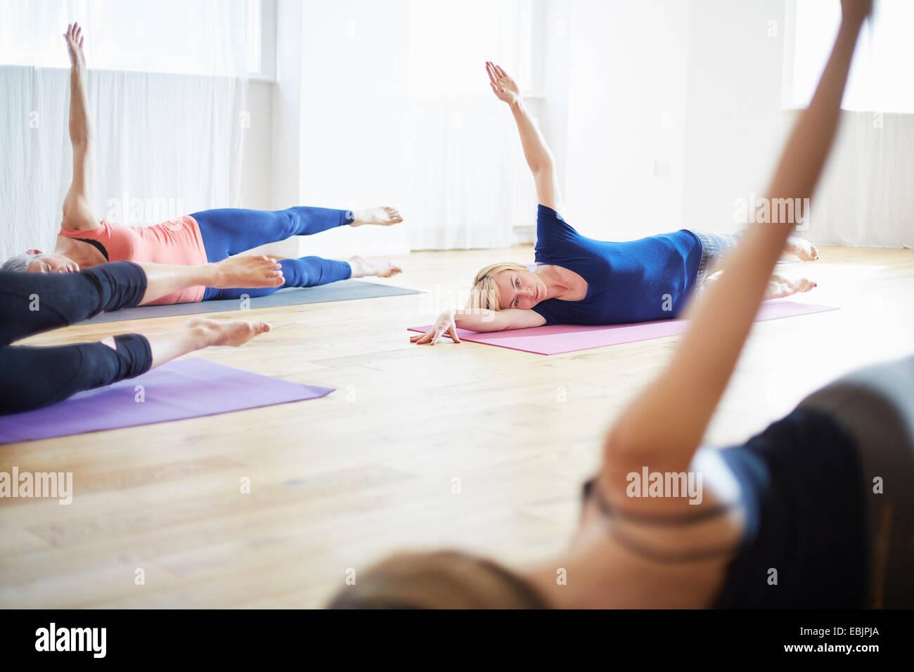 Cuatro mujeres acostado en el lado con los brazos levantados en clase de pilates Imagen De Stock