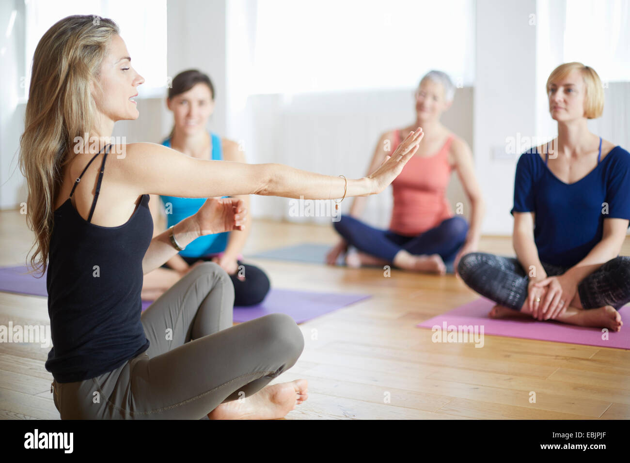 Tutor de hembras maduras con los brazos extendidos en clase de pilates Imagen De Stock