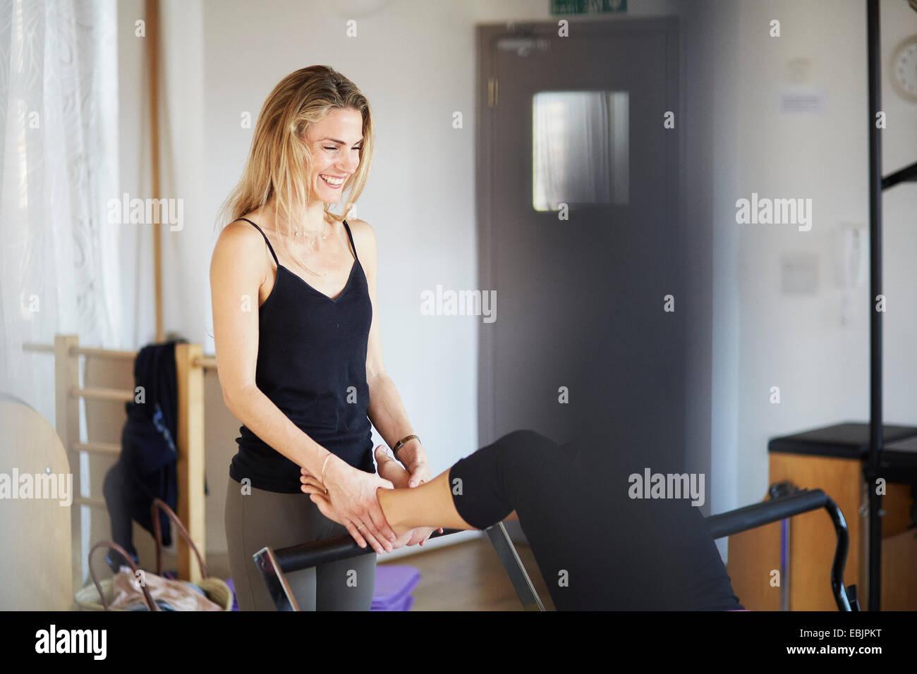 Profesor manteniendo los pies del estudiante de sexo femenino acostado sobre reformador de pilates gimnasio Imagen De Stock