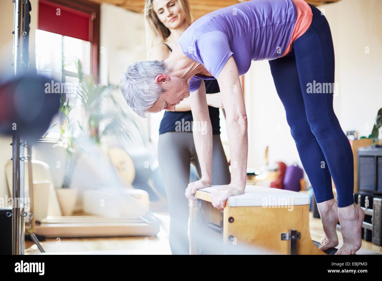 Estudiante de hembras maduras agacharse combo silla de pilates gimnasio Foto de stock