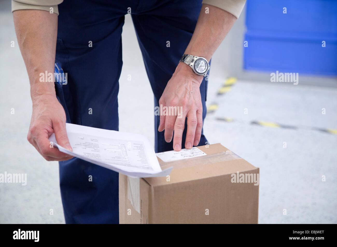 Comprobación de trabajador sanitario de envases en el almacén Imagen De Stock