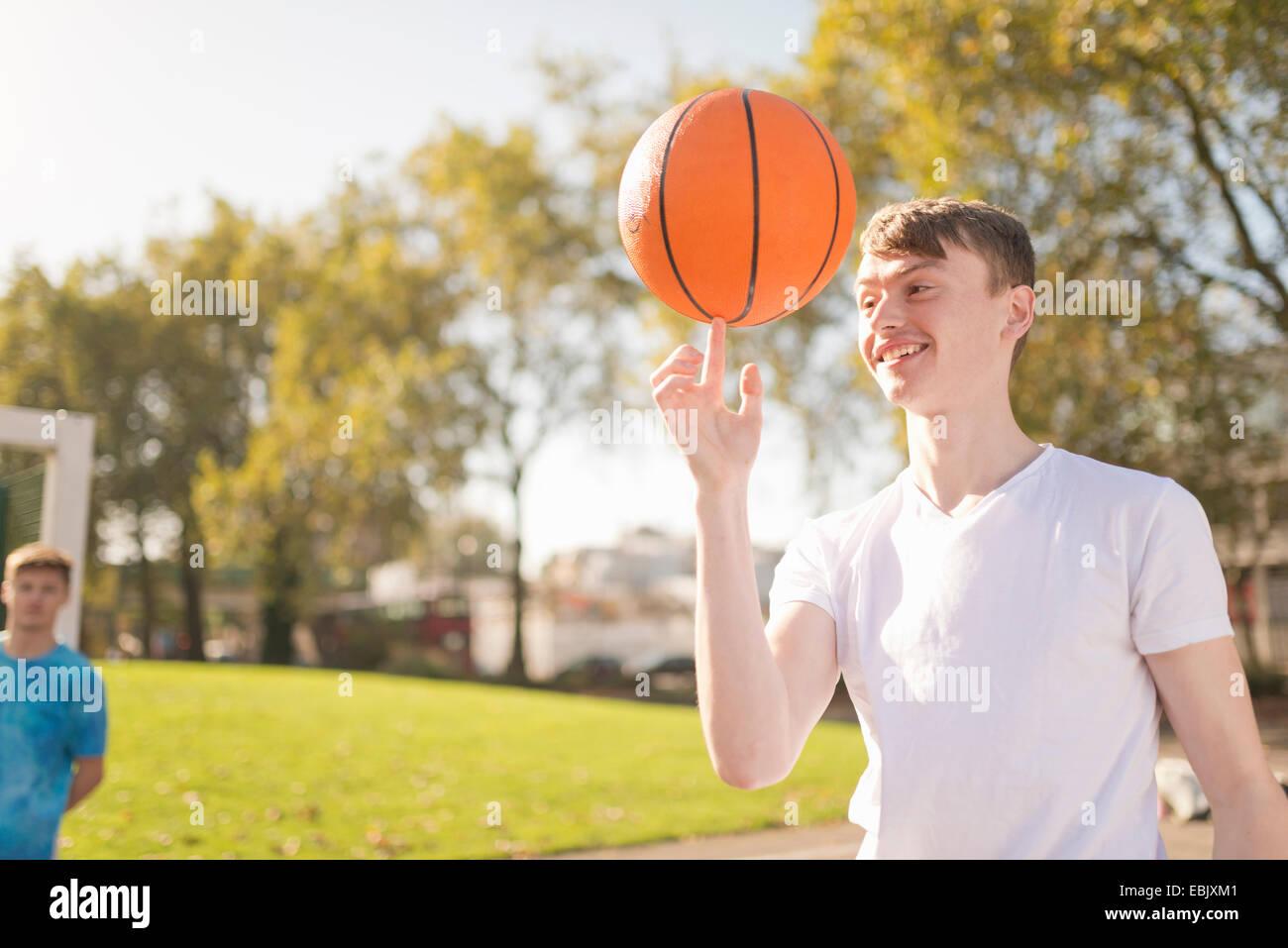 Sonriente joven jugador de baloncesto masculino de baloncesto de equilibrio sobre el dedo Imagen De Stock