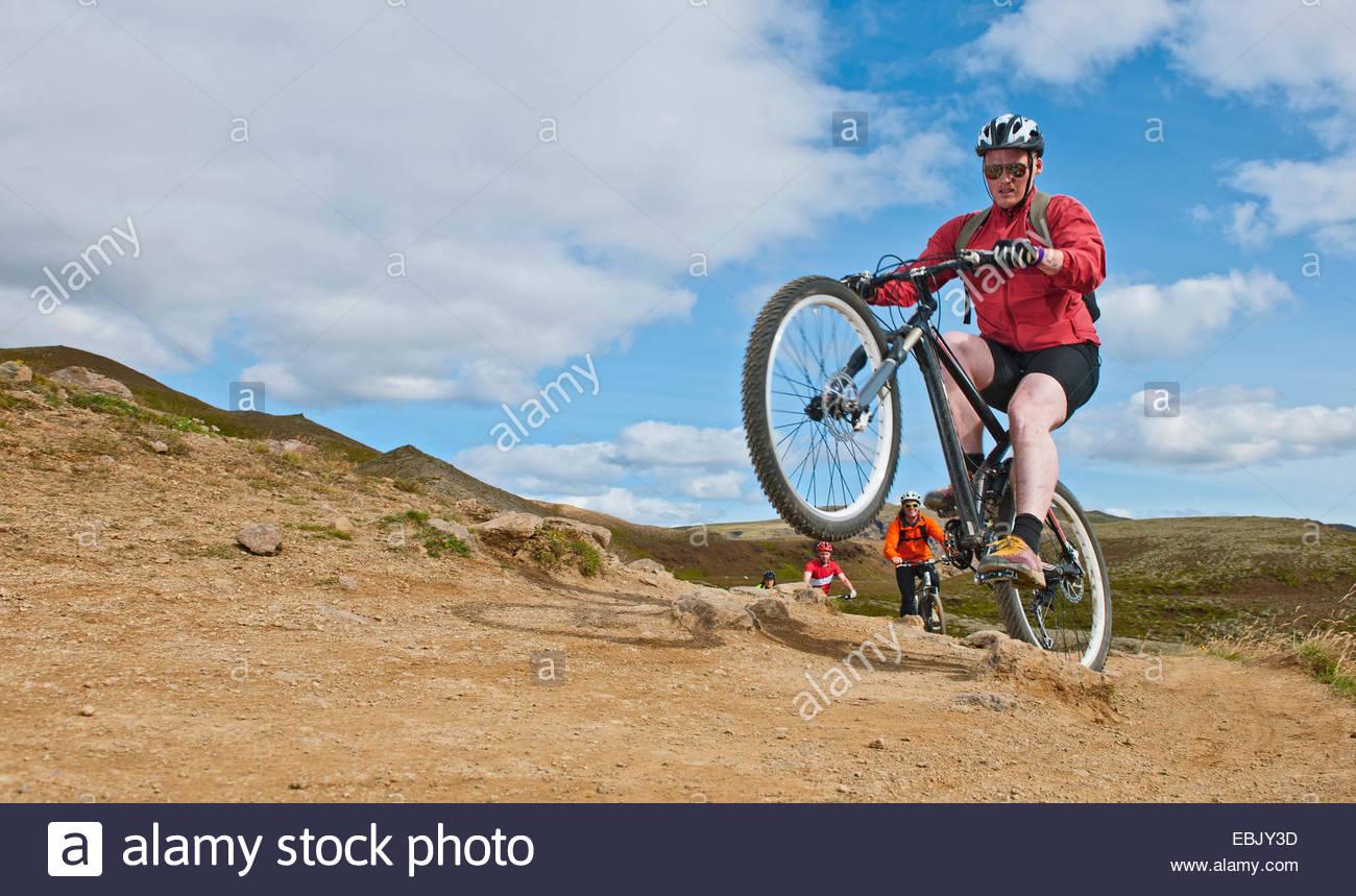 Ciclistas de montaña a través del valle Reykjadalur, Suroeste de Islandia Imagen De Stock