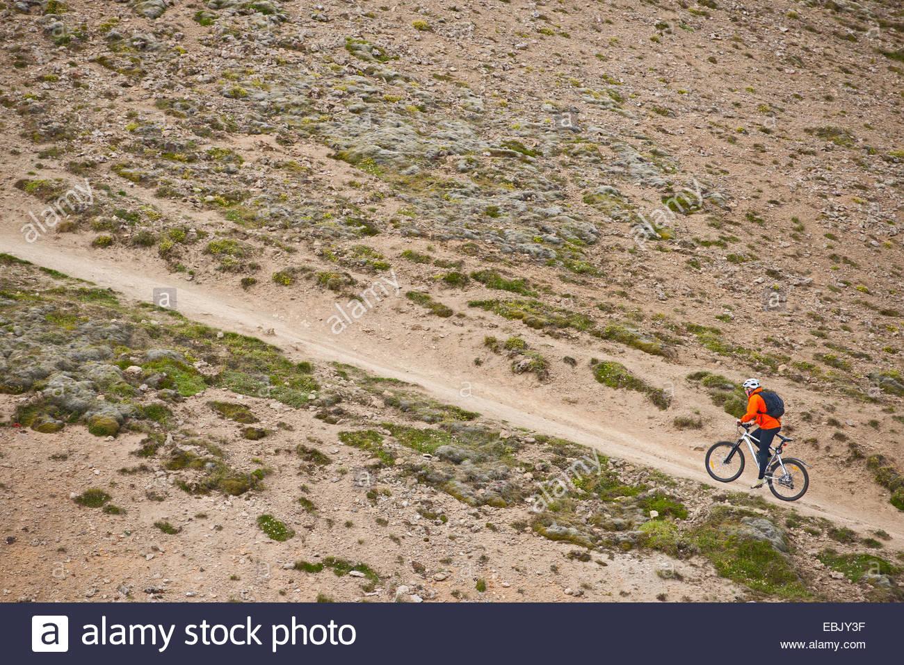 Macho ciclista de montaña en bicicleta de dirt track, empinado valle Reykjadalur, Suroeste de Islandia Imagen De Stock