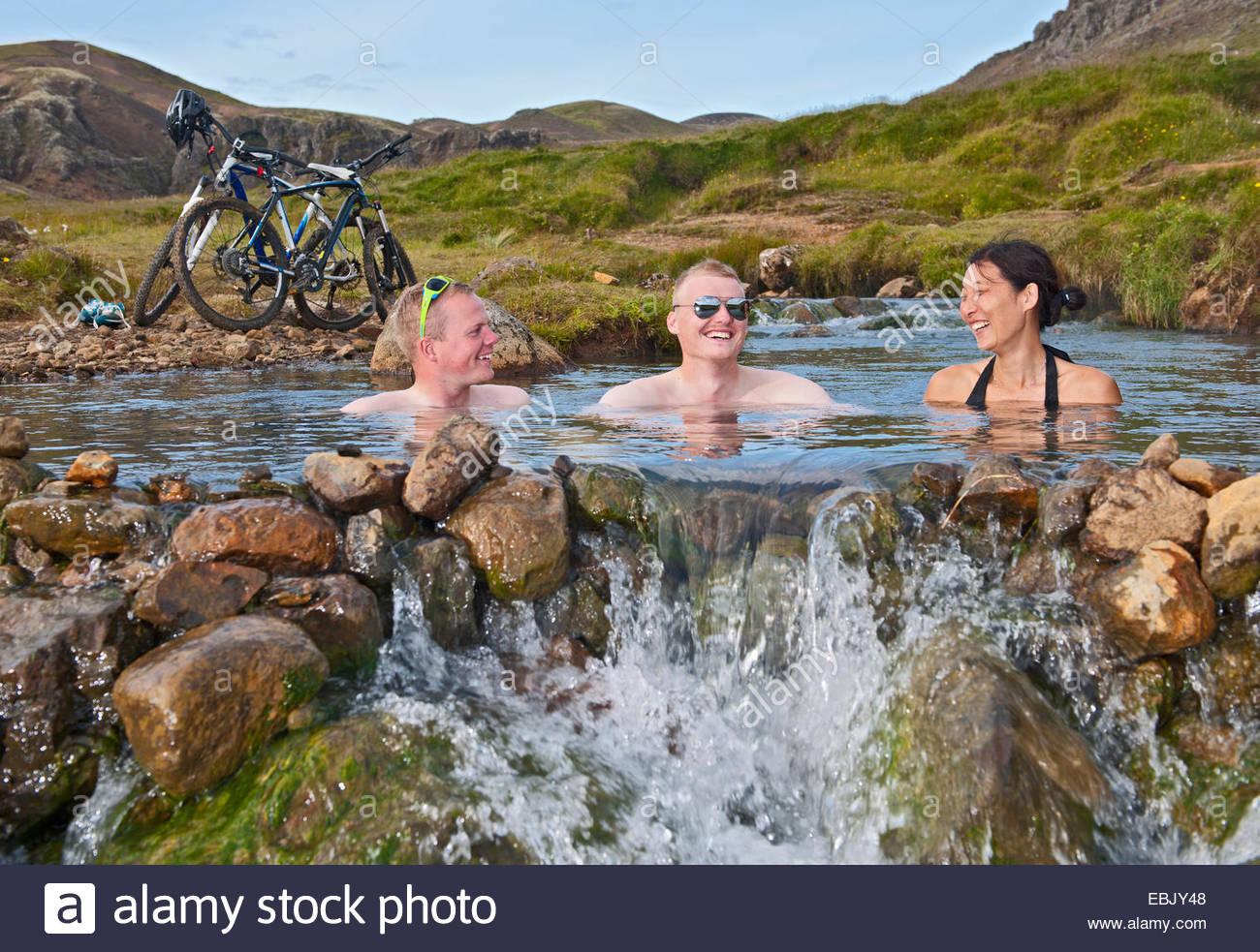 Ángulo de visión baja de tres ciclistas de montaña de bañarse en el río caliente, valle Imagen De Stock