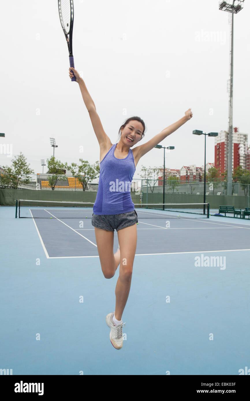 Joven Jugador de tenis femenino saltando de alegría en la cancha de tenis Imagen De Stock