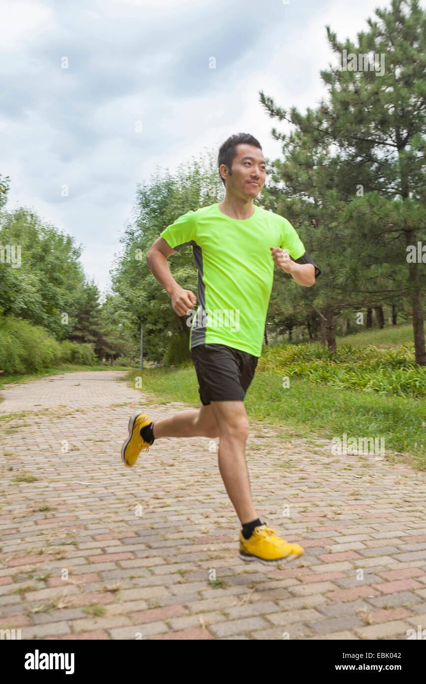 Macho joven corredor corriendo en el parque Imagen De Stock