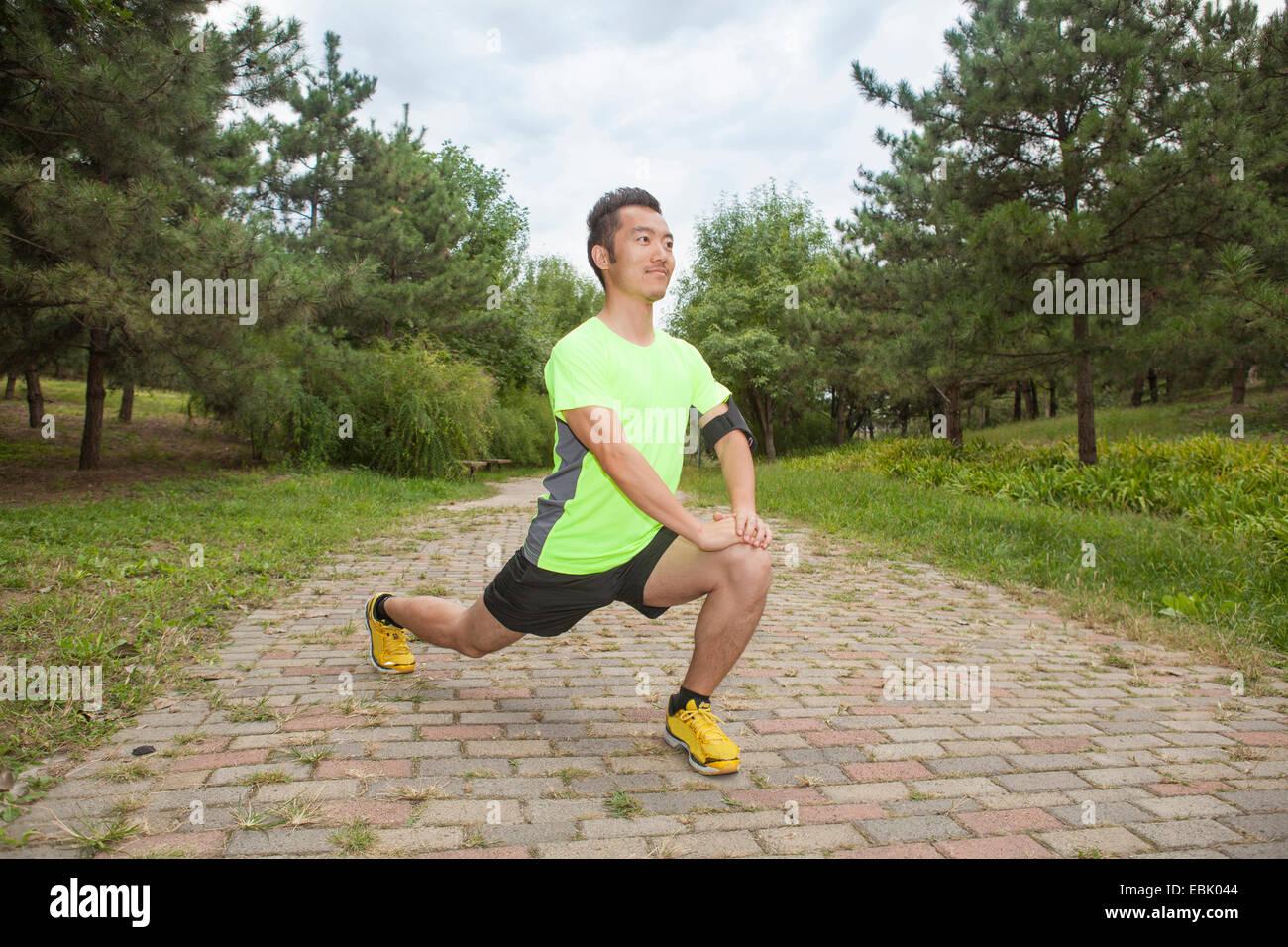 Macho joven corredor estirar las piernas en la posición de estacionamiento Imagen De Stock