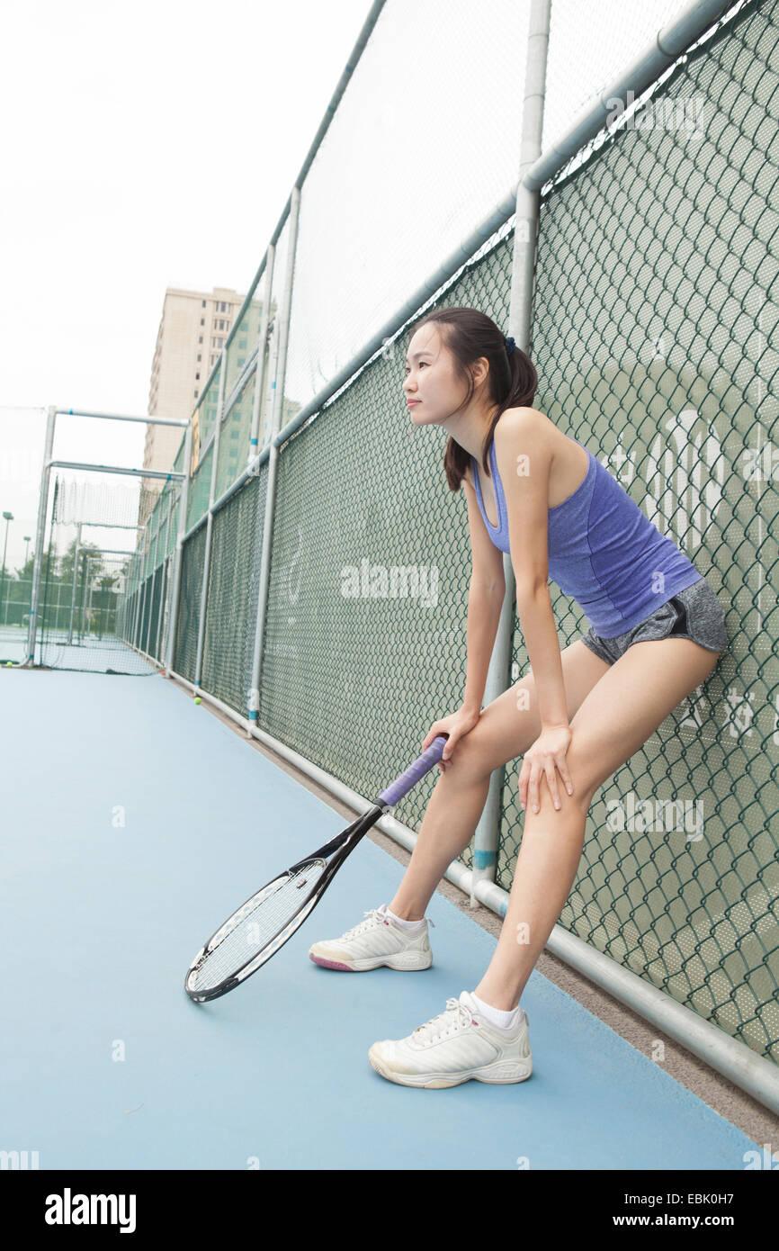 Joven Jugador de tenis femenino inclinado contra la valla en la pista de tenis Imagen De Stock