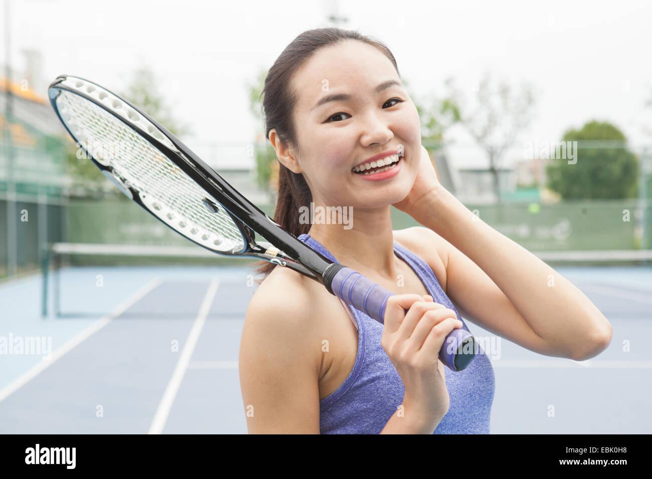 Retrato de mujer joven jugador de tenis en la cancha de tenis Foto de stock