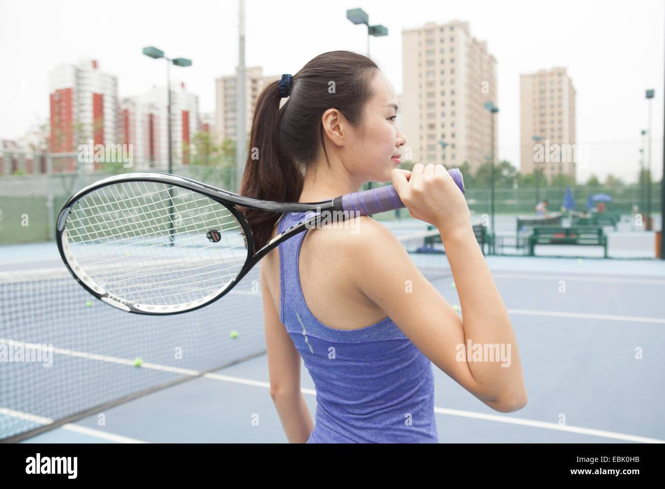 Joven Jugador de tenis femenino con la raqueta de tenis sobre el hombro de cancha de tenis Foto de stock