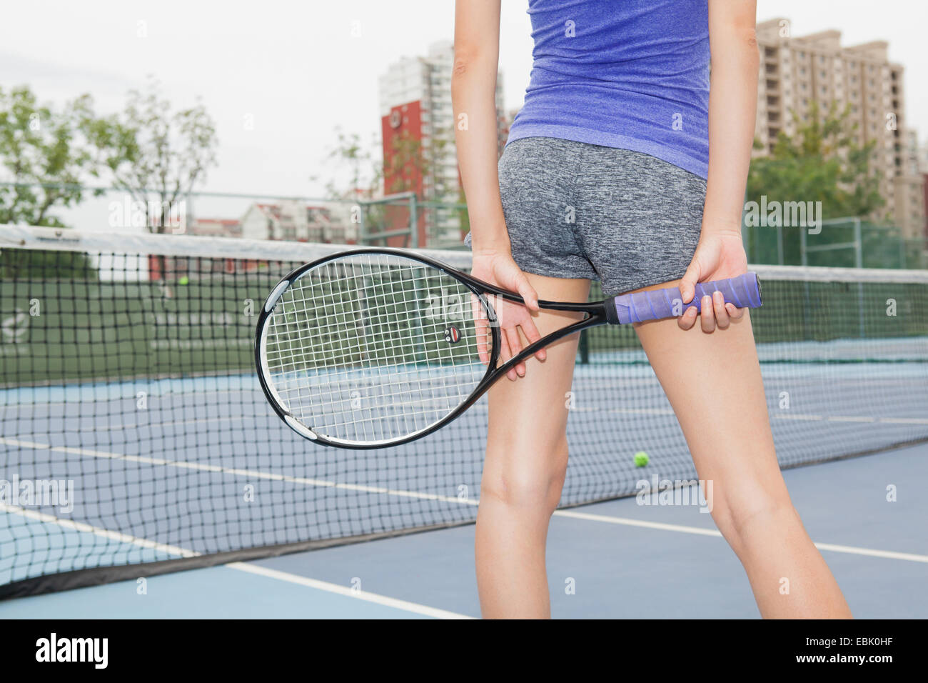 Vista trasera recortada del joven jugador de tenis en la cancha de tenis Foto de stock