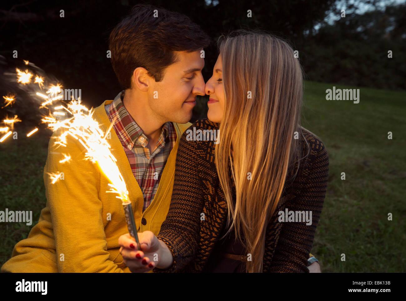 Pareja joven la nariz con nariz en park la celebración de fuegos artificiales espumoso Imagen De Stock