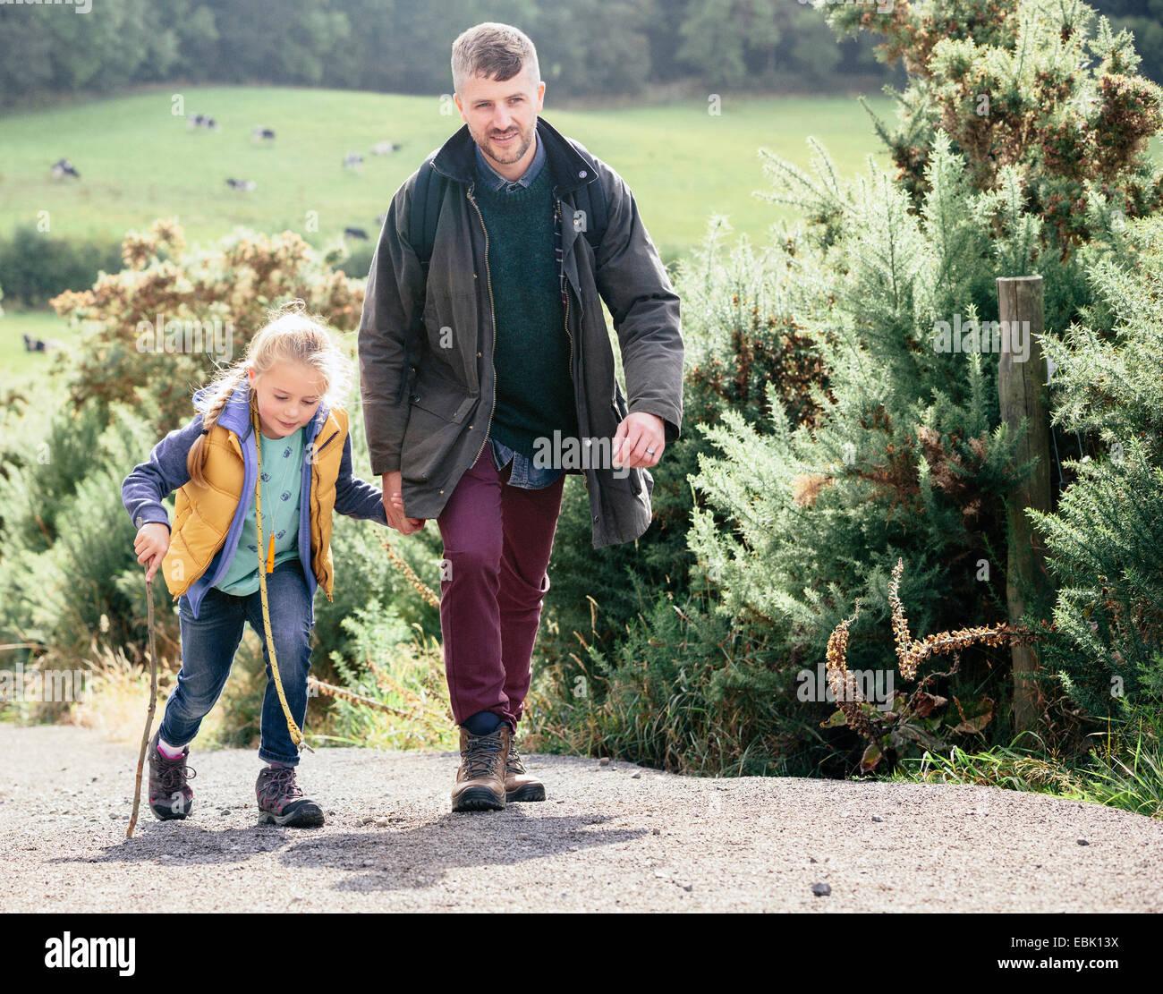 El padre y la hija de senderismo en carretera rural Imagen De Stock