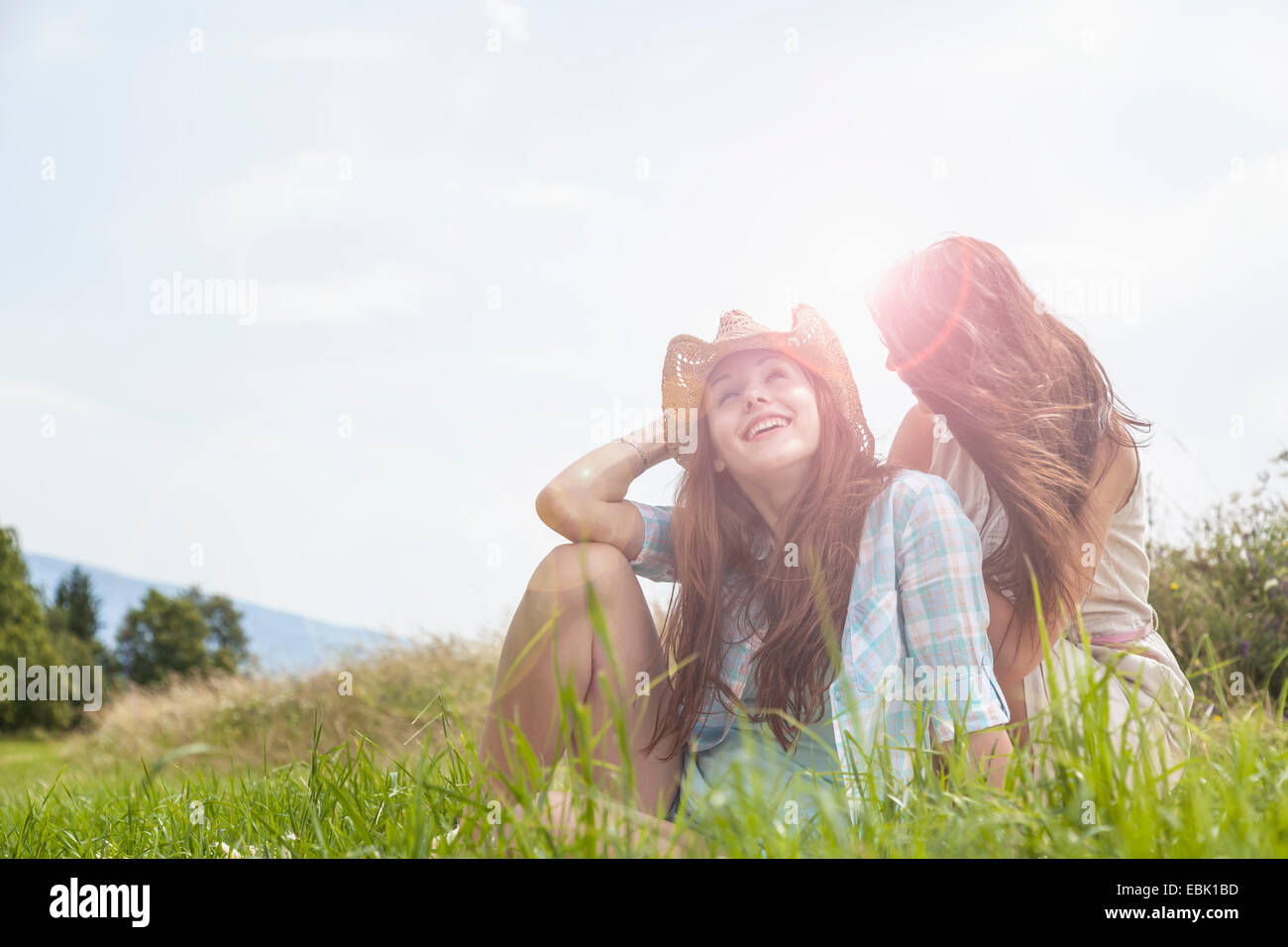 Dos jóvenes mujeres sentadas conversando en césped Imagen De Stock