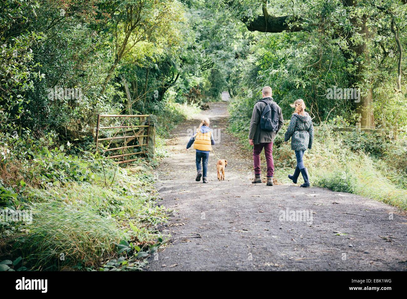 Padre y dos niñas paseando a un perro en la carretera rural Foto de stock
