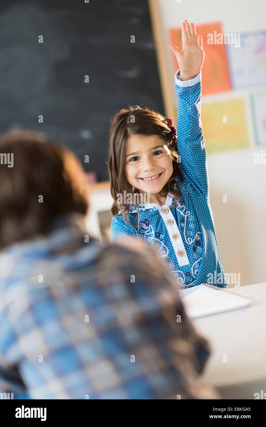 Los alumnos (6-7) El aprendizaje en aula, Chica (6-7) levantando la mano Imagen De Stock