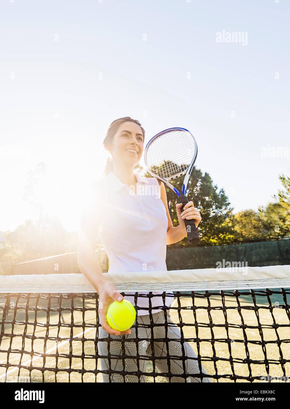 Ee.Uu., Florida, Júpiter, Retrato de mujer joven de pie por net, sosteniendo pelota de tenis y raqueta de tenis Imagen De Stock