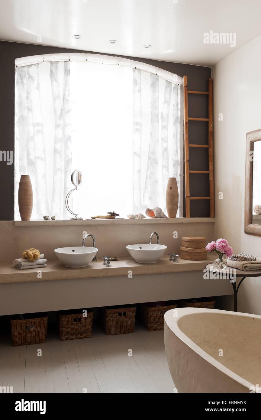 Persianas de Ikea en el cuarto de baño con bañera de hormigón. El ...
