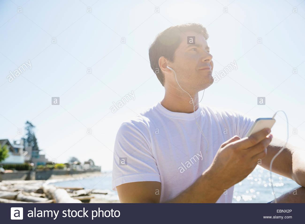 Runner escuchar el reproductor de mp3 en la playa Foto de stock