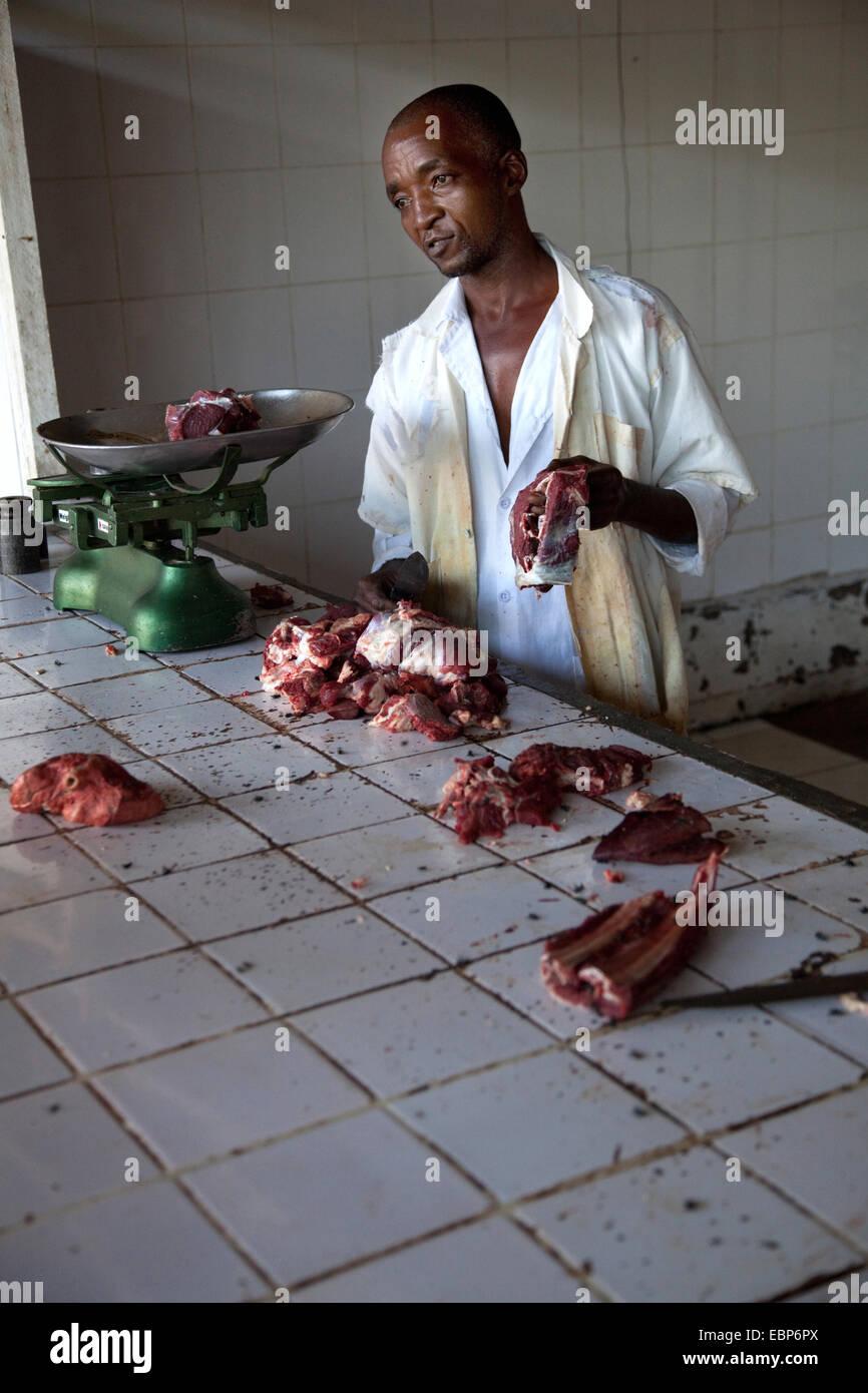 Carnicero en mercado público ofreciendo carne de cabra fresco a clientes en malas condiciones hiegene Nyamirambo, Imagen De Stock