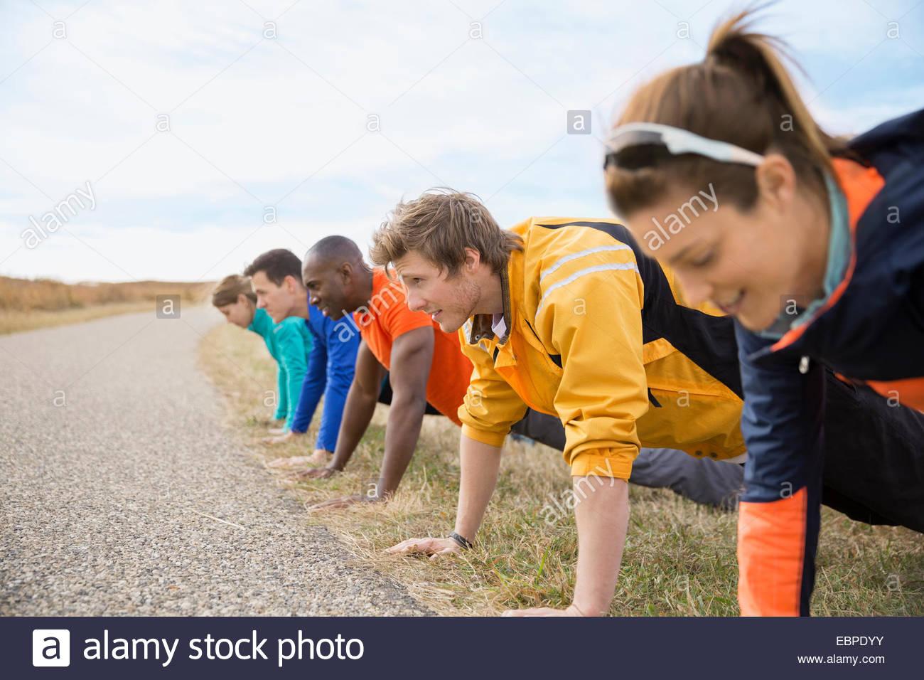 Grupo haciendo push-ups en una fila Imagen De Stock