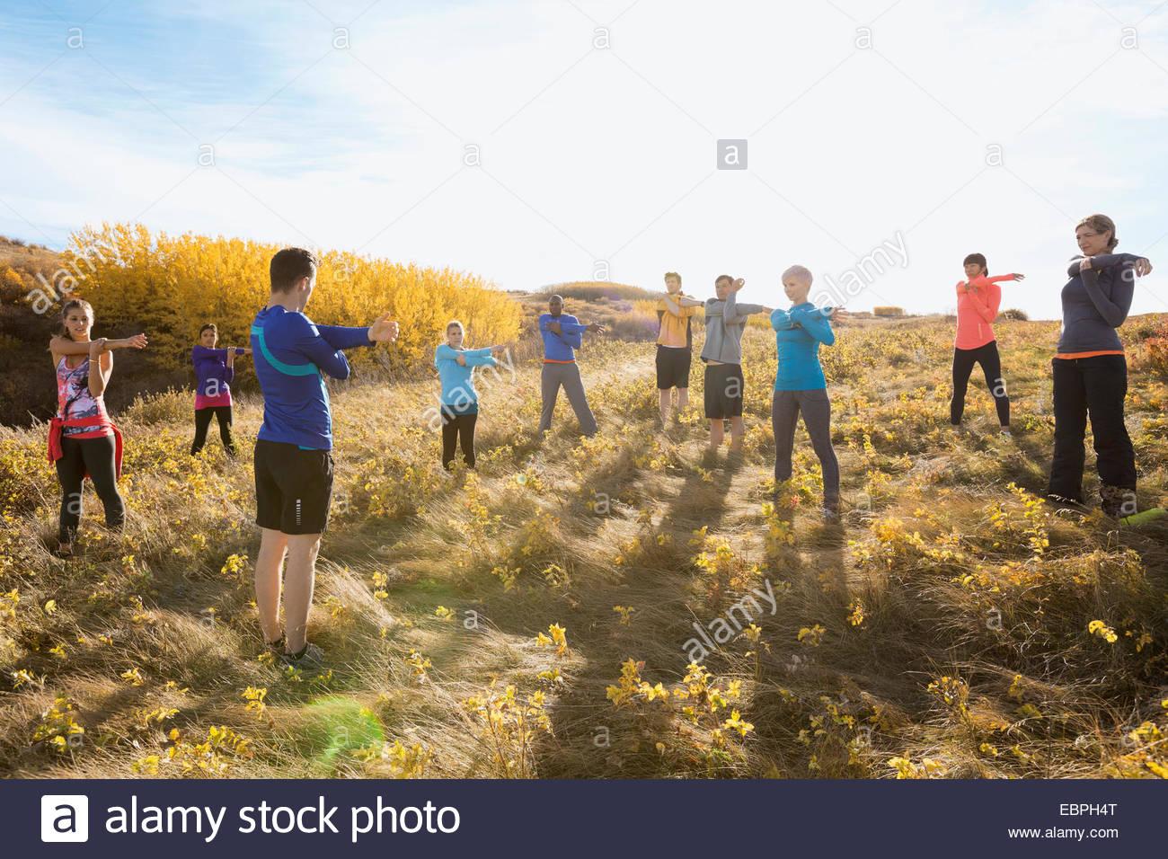 Grupo de fitness estiramiento en el soleado campo rural Imagen De Stock