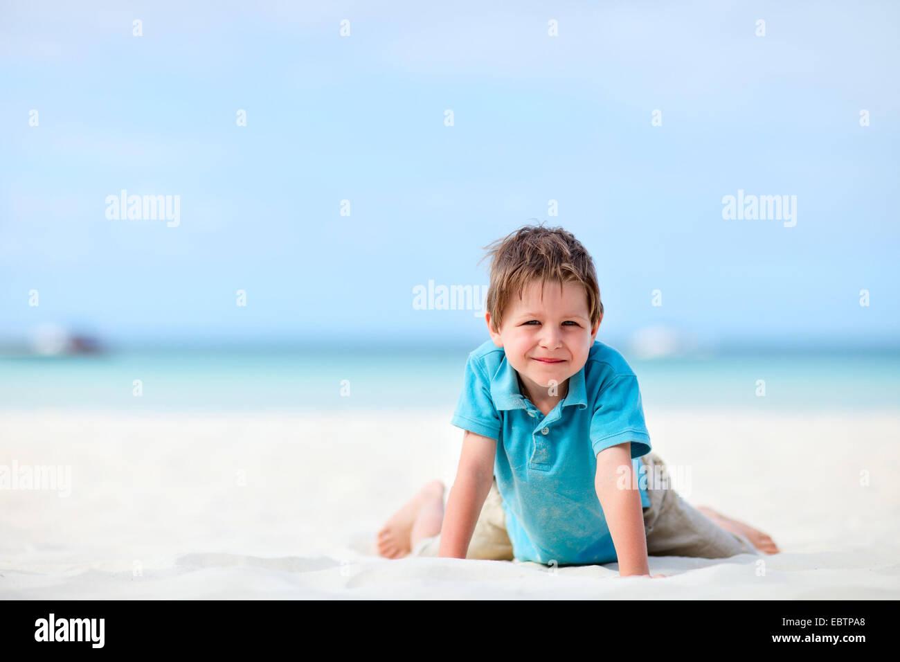 Niño de 5 años de edad rodillazos en playa tropical Foto de stock