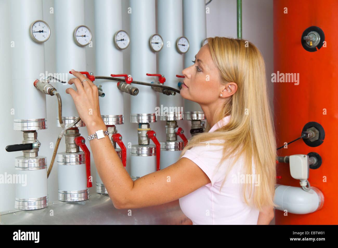Mujer joven en la sala de calderas, la lectura del contador de agua Imagen De Stock