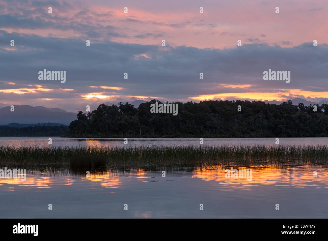 Amanecer en el lago, Ruatapu Mahinapua, región de la Costa Oeste, Nueva Zelanda Foto de stock