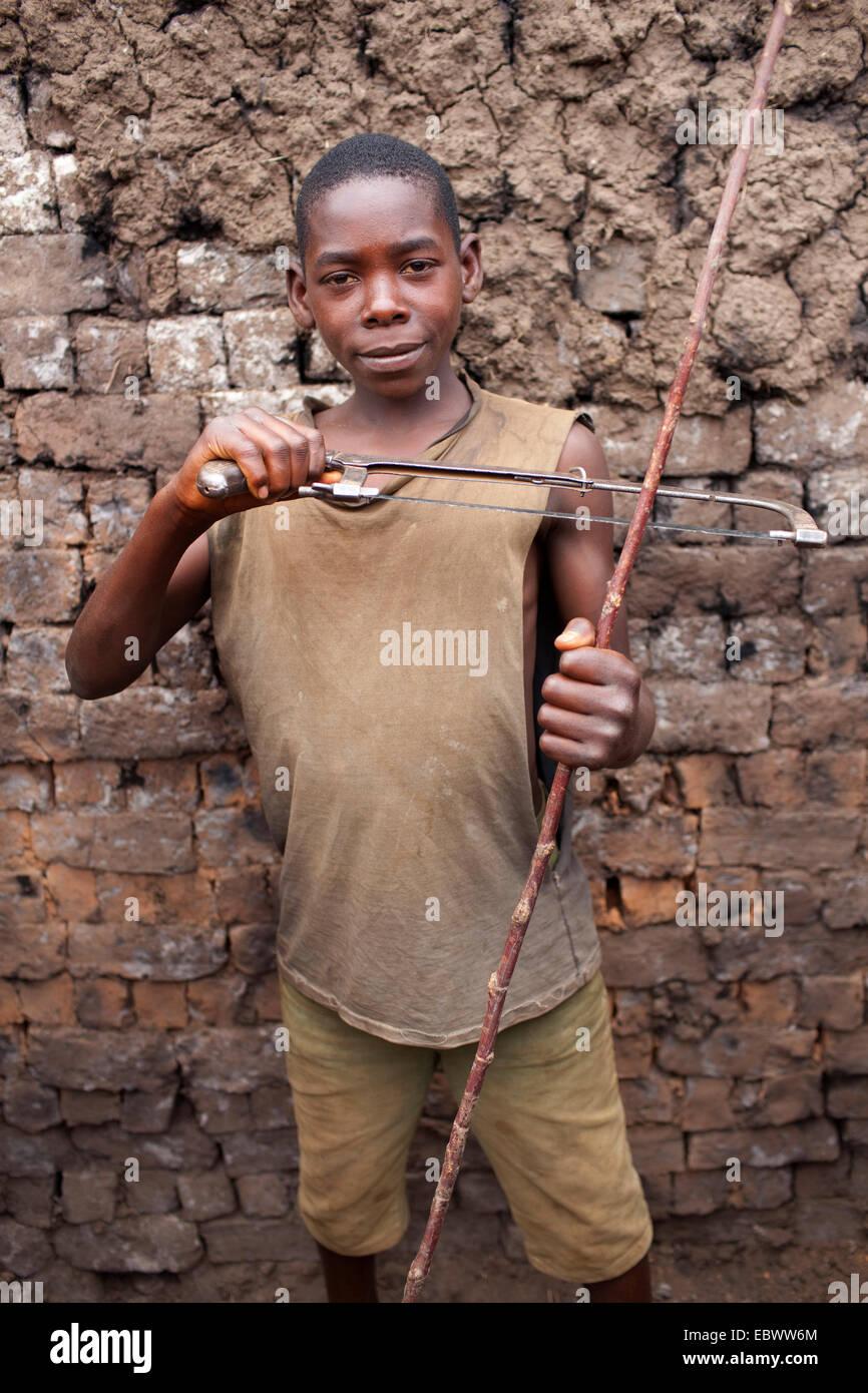 Boy mostrando sierra y rama, Burundi, Karuzi, Buhiga Foto de stock