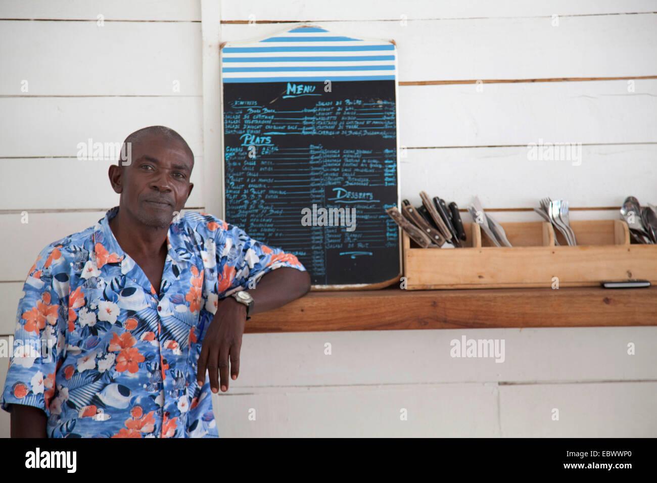 Hombre de pie en un mostrador con cubertería y menú, Burundi, Bujumbura Mairie, Bujumbura Imagen De Stock