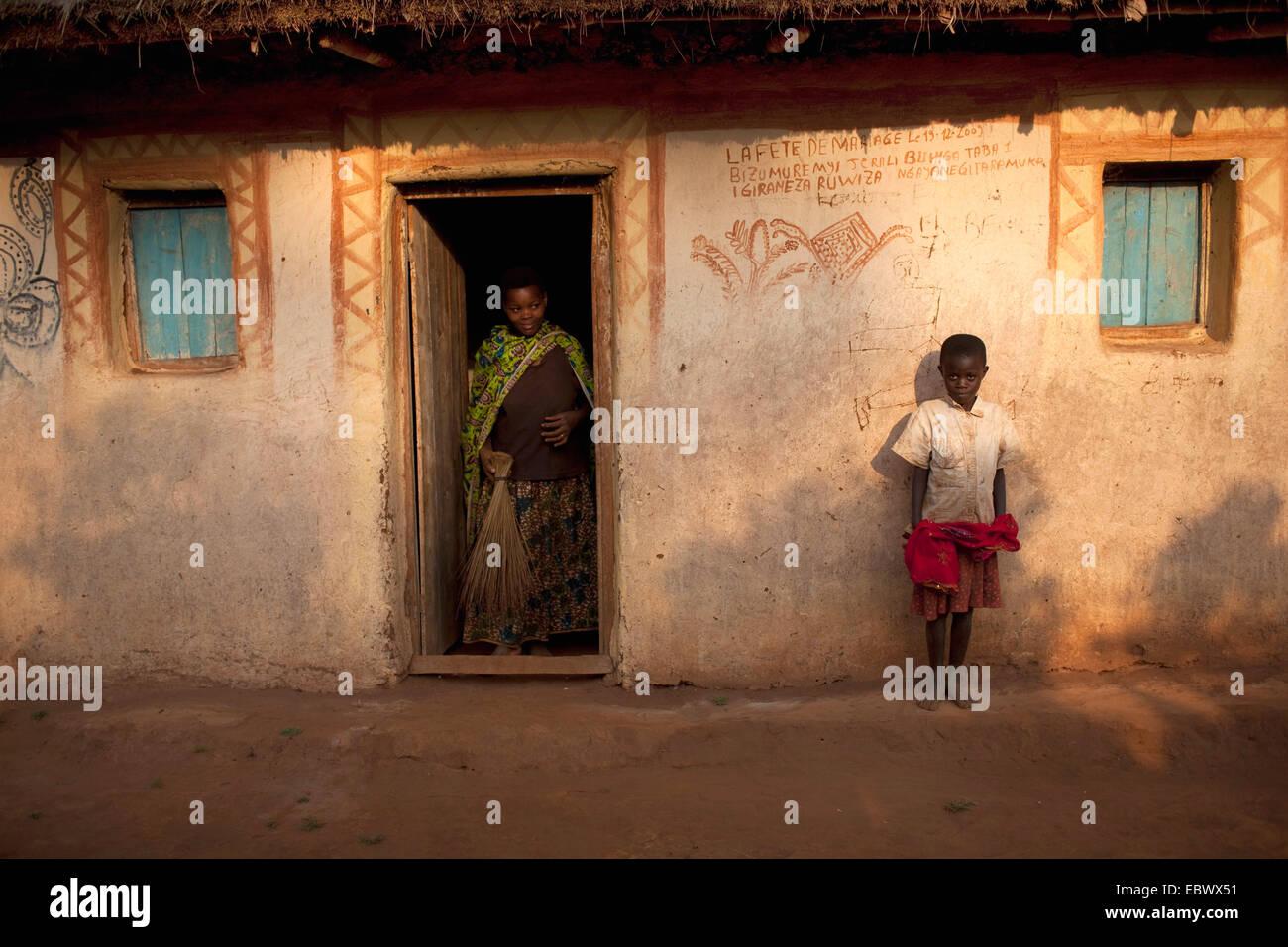 Mujer con besom de pie en la entrada, el Niño recostado contra la fachada, Burundi, Karuzi, Buhiga Foto de stock