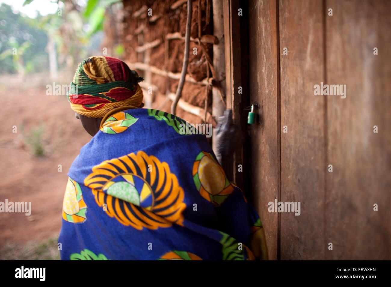 Anciana de salir de su casa y cerrar la puerta, Burundi, Karuzi, Buhiga Imagen De Stock