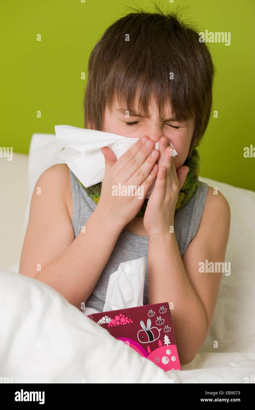 Niño enfermo en la cama sopla su nariz Foto de stock