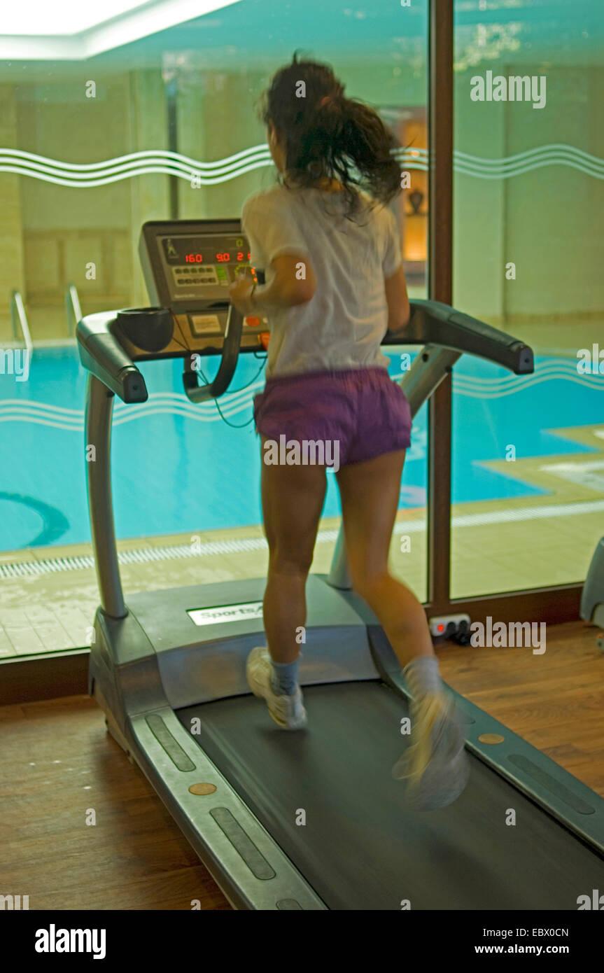 Joven en un gimnasio riendo mientras que correr sobre una cinta sin fin Imagen De Stock
