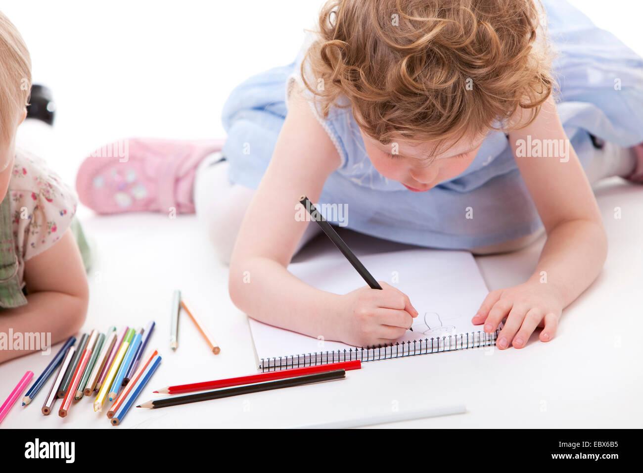 Las niñas tirados en el groud de dibujo con lápices Foto de stock