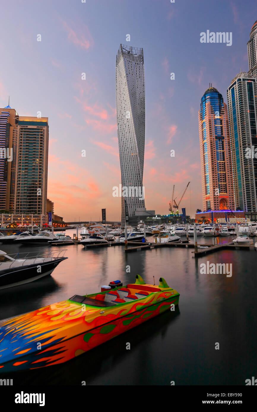 Horizonte de Dubai Marina. Barco de la velocidad en la parte delantera y en la parte posterior de la torre retorcida. Foto de stock