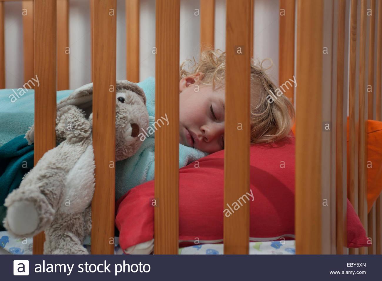 Un niño pequeño (2 1/2 años) duerme en su cuna durante la hora de la siesta por la tarde. Imagen De Stock