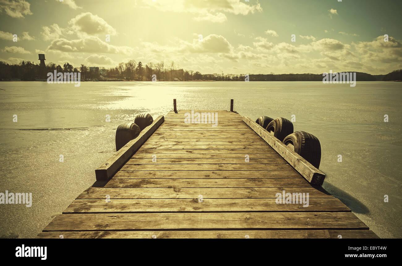 Imagen de tonos retro vintage de un muelle sobre el lago congelado. Foto de stock
