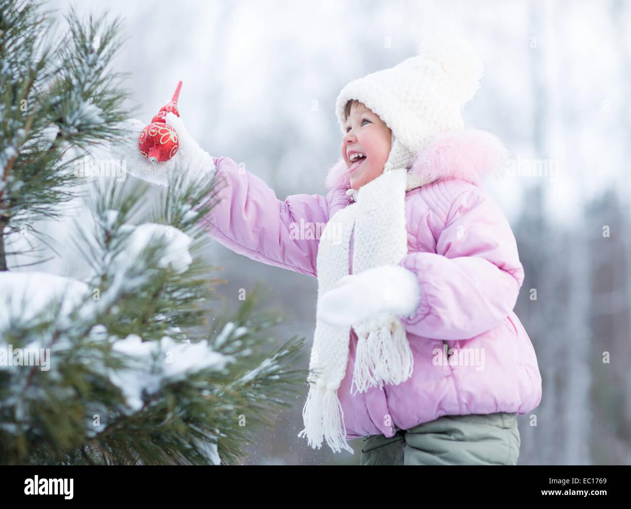 Niño feliz haciendo adornos del árbol de Navidad en el exterior Imagen De Stock
