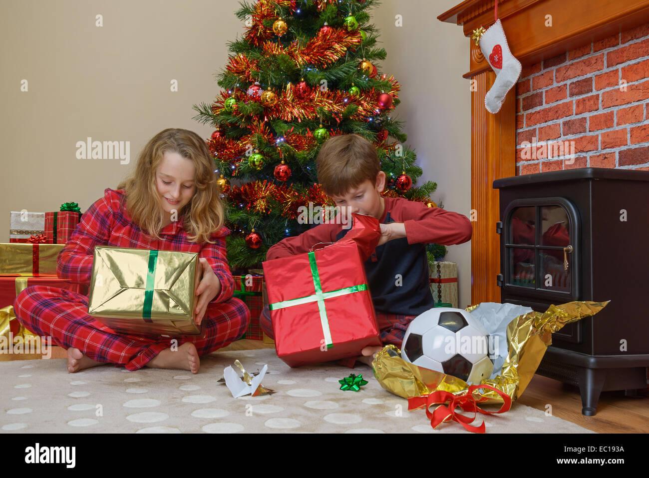 Dos niños, un niño y una niña, abriendo sus regalos en la mañana de Navidad. Imagen De Stock