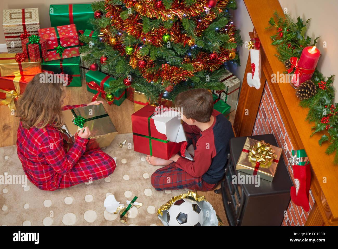 Fotografía aérea de niños, un chico y una chica, sentados por el árbol desenvolver sus regalos Imagen De Stock
