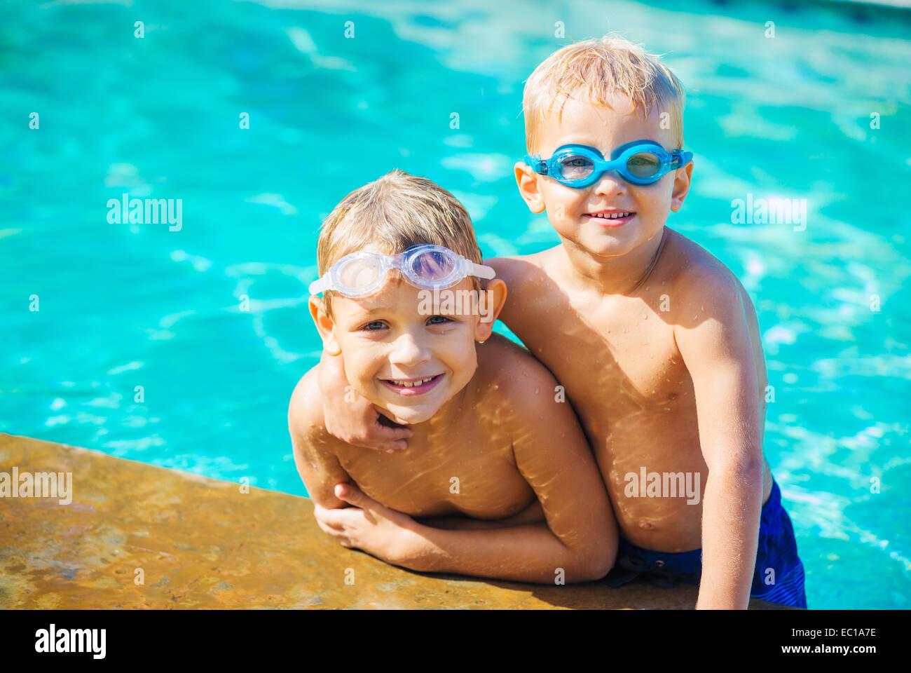 Dos adorables chicos a divertirse en la piscina. Divertidas vacaciones de verano. Imagen De Stock