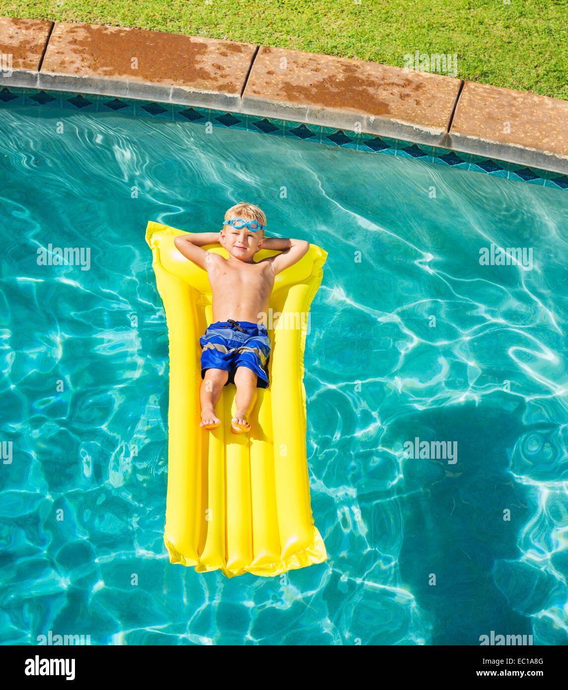 Joven relajarse y divertirse en la piscina en balsa amarilla. Divertidas vacaciones de verano. Concepto de estilo Imagen De Stock